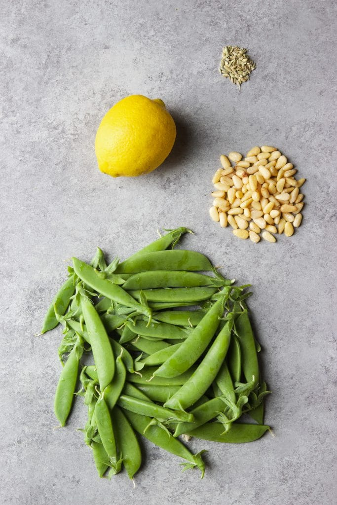fresh snap peas, pine nuts, a lemon and fennel seeds on a gray board