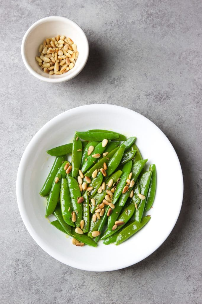 sautéed snap peas with toasted pine nuts on a white round plate. A small white bowl of toasted pine nuts on a gray board