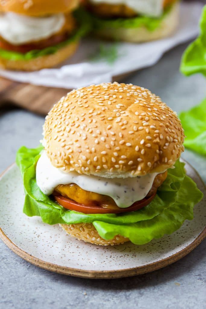 cheddar ranch chicken burger on a round plate. Close up image.