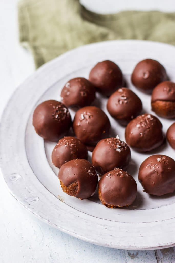a white plate with chocolate energy balls, sprinkled with sea salt
