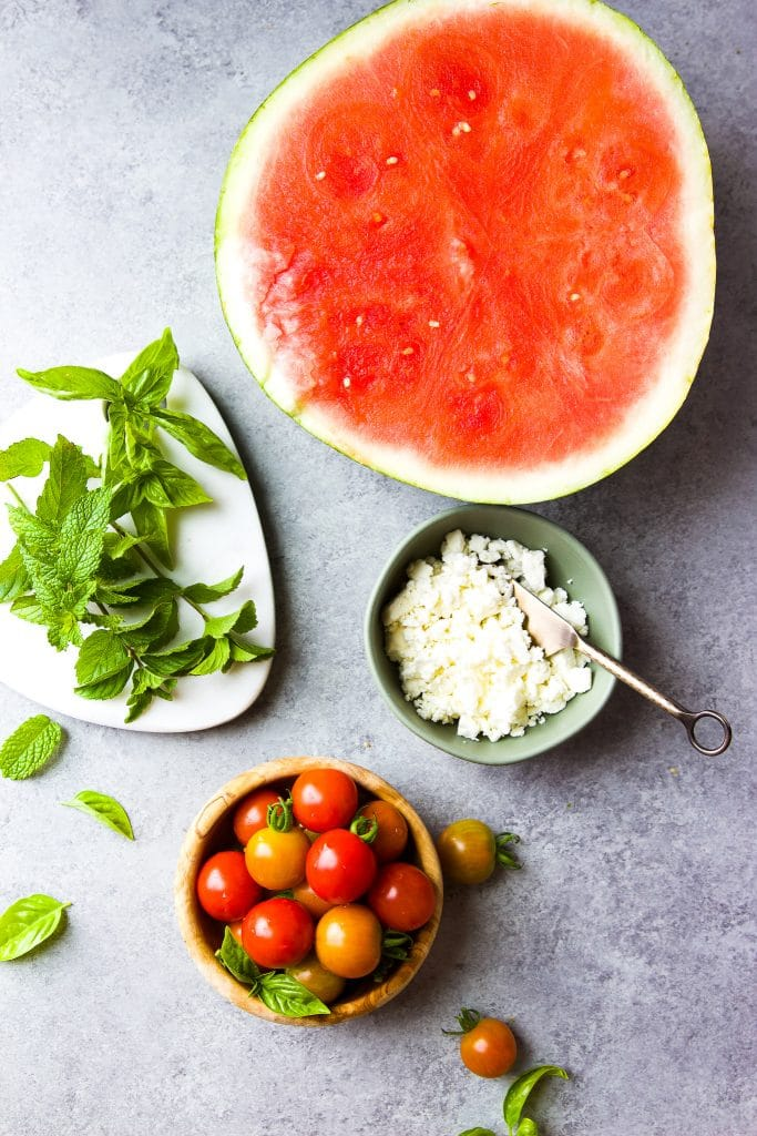 watermelon salad ingredients. large watermelon halved, fresh mint and basil leaves. Feta cheese and tomatoes in small bowls
