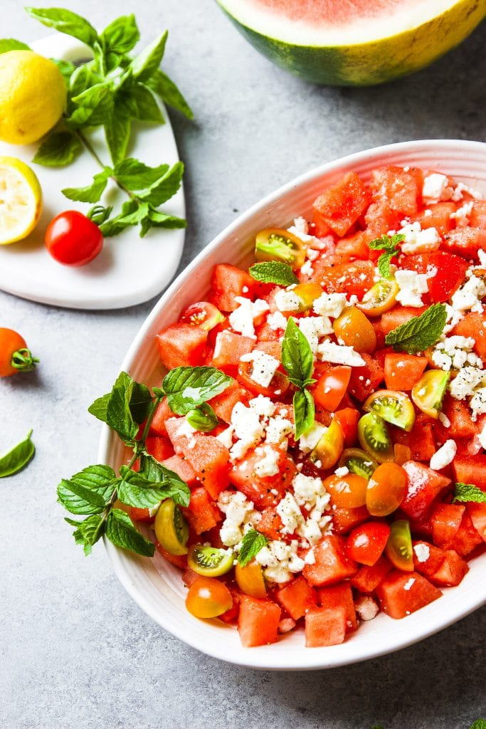 watermelon feta salad with fresh mint and basil leaves. garden tomatoes. served in large white oval bowl. fresh leaves around the table