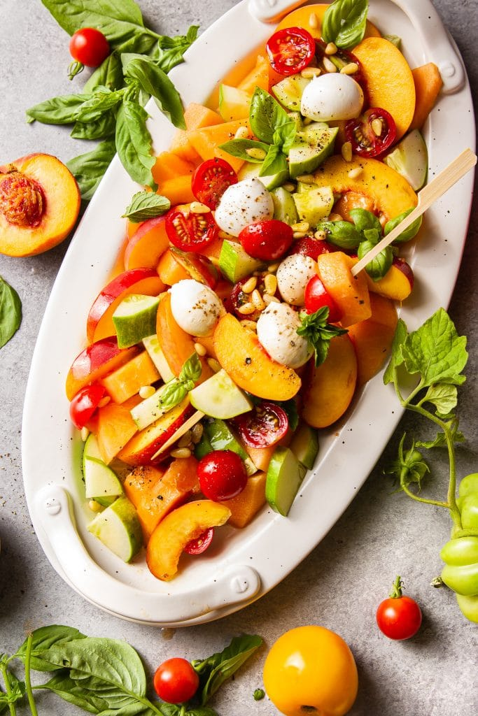 fruit salad in a white oval platter with cut up cantaloupe, peach slices, cherry tomatoes, cucumber slices and fresh mozzarella. Topped with basil and mint leaves.