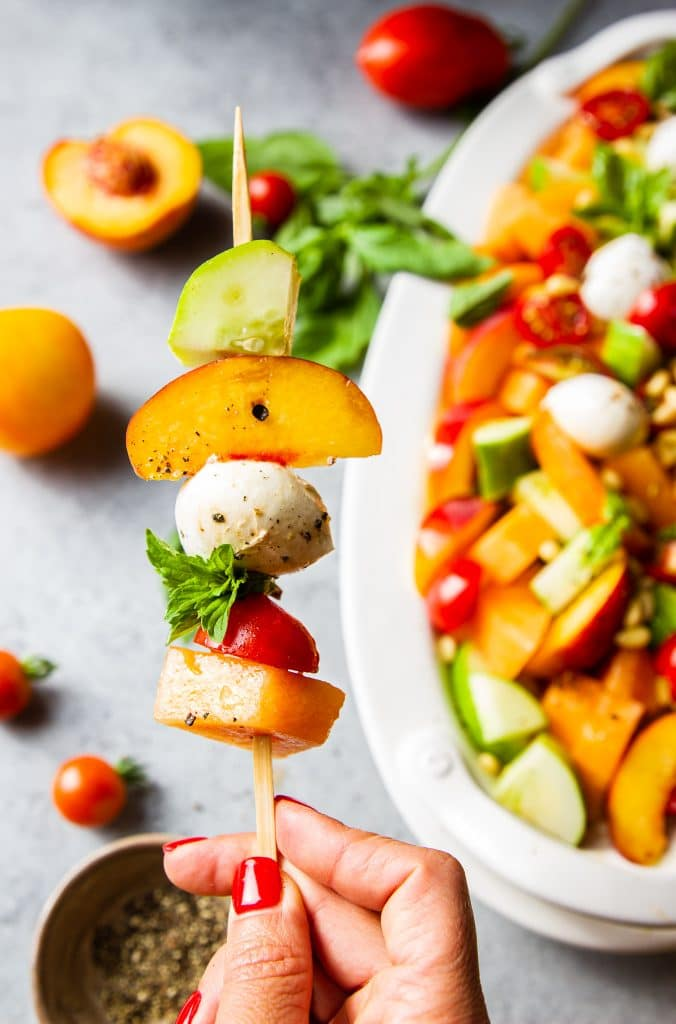 fruit salad in skews with a hand holding it. cucumber, peach slice, fresh mozzarella cheese, mint leaf, cherry tomato and cantaloupe.