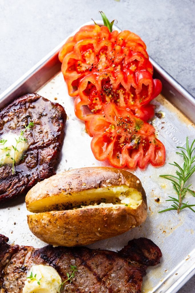 grilled steak with baked potato and tomato slices, in a baking sheet with fresh herbs and sea salt