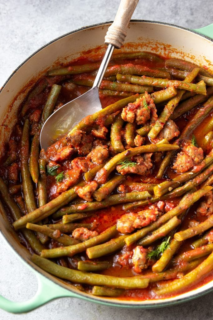 green beans cooked in tomato sauce with sausage, in large skillet