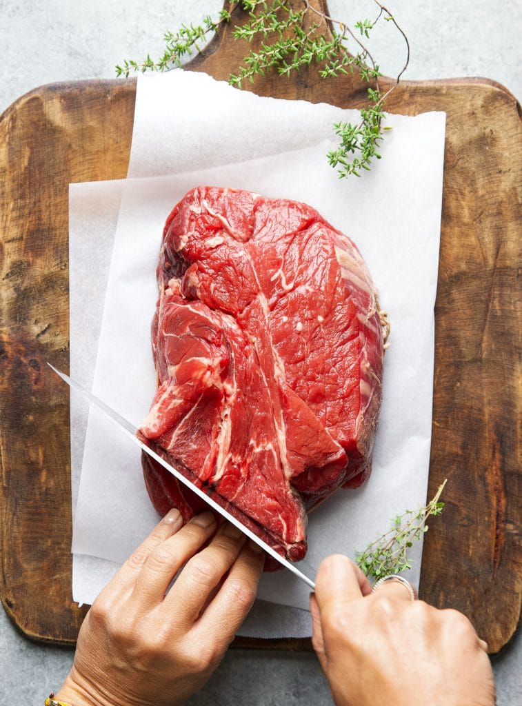 Hand slicing a piece of chuck meat on a cutting board.