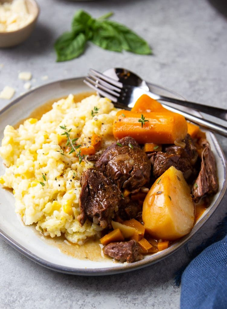 Beef stew on a plate with carrots and potatoes. Served alongside corn risotto. Fresh cheese and herbs on the table