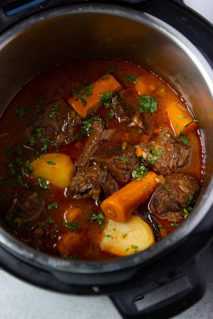 Beef stew in instant pot with carrots and potatoes. Fresh herbs on top