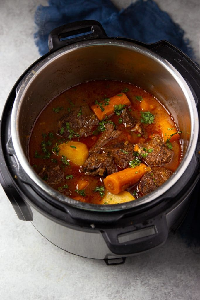 Beef stew in instant pot with carrots and potatoes. Fresh herbs on top and blue towel on the table