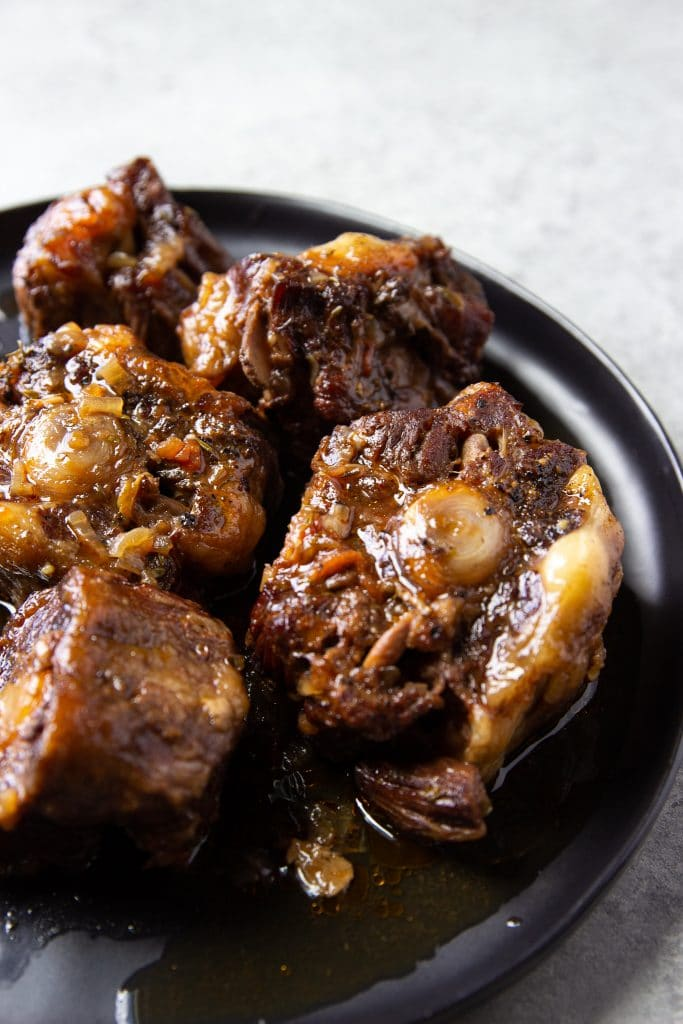 oxtails served on a round black plate