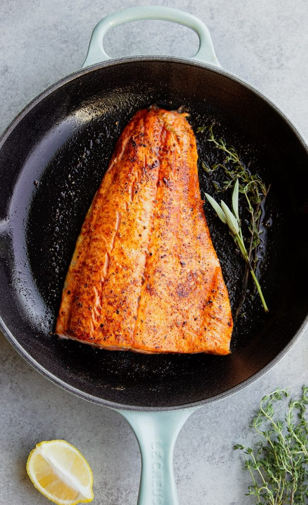 salmon filet in a cast iron skillet with herbs