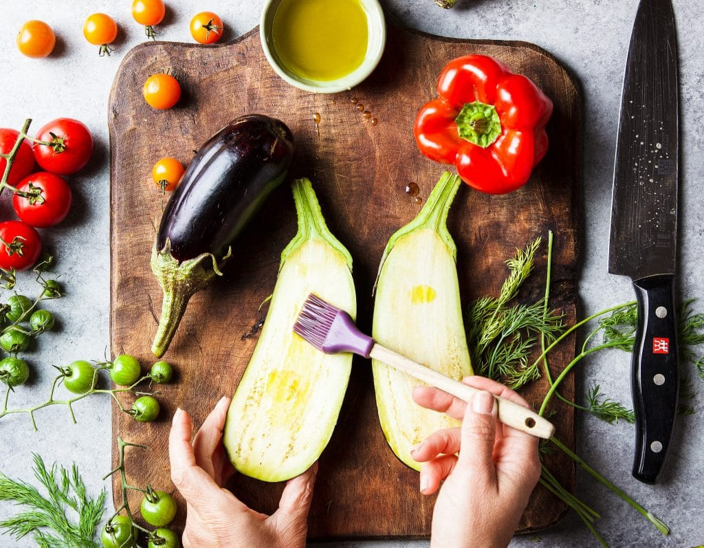ingredients for stuffed eggplant on a wooden cutting board. A hand brushing an eggplant with olive oil. Green, orange and red tomatoes. One red bell pepper, a small onion. Fresh dill herb