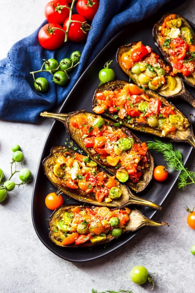 Eggplant stuffed with tomatoes served on a black oval serving plate. Green and red tomatoes on the table. A blue kitchen cloth