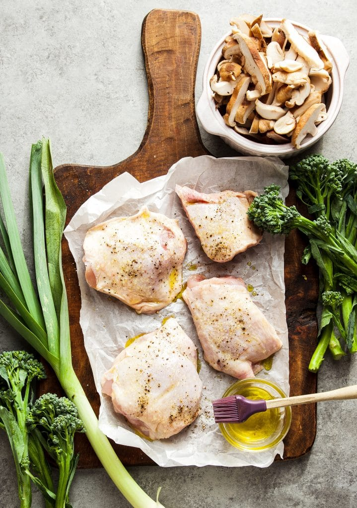 Chicken thighs seasoned with oil, salt and pepper on a parchment paper. Broccoli and leek on a cutting board