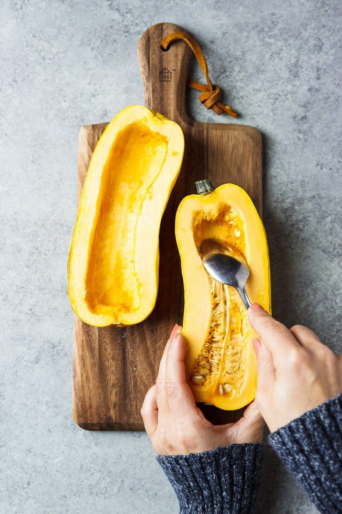 delicata squash being cleaned with a spoon removing seeds.