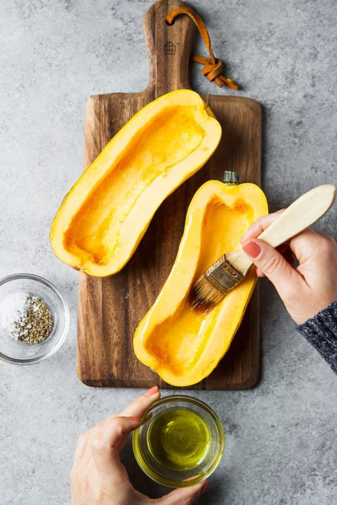delicata squash being brushed with olive oil