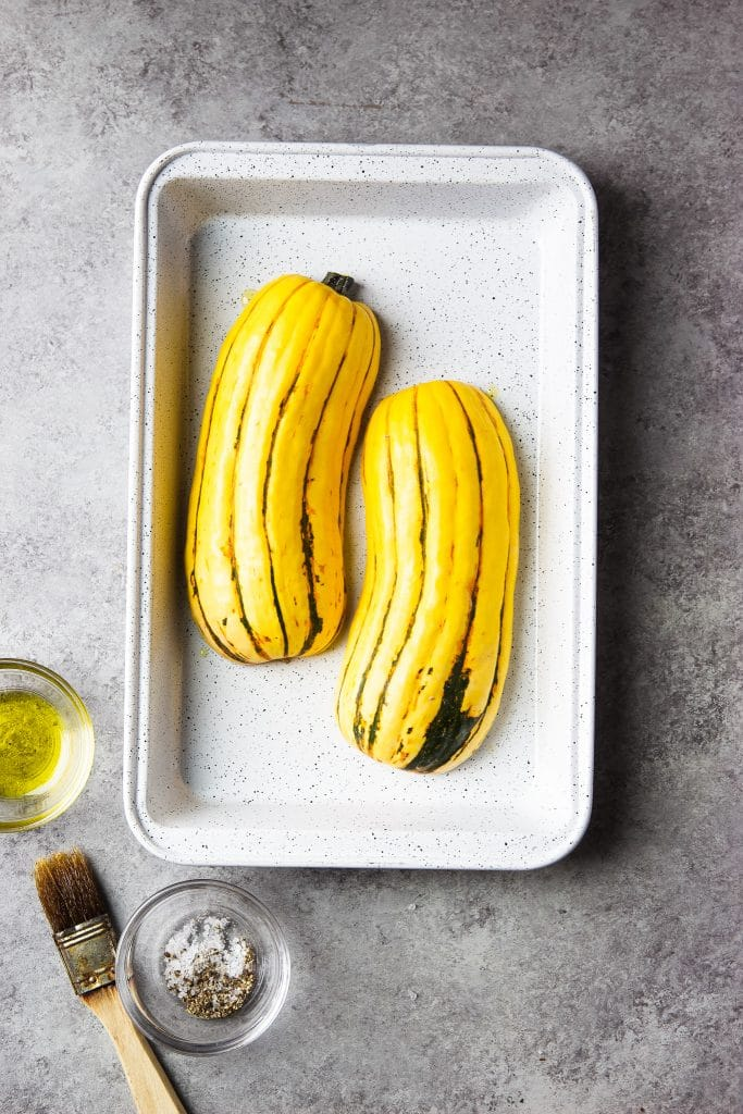 delicata squash in a roasting plan. Seasonings on the table.