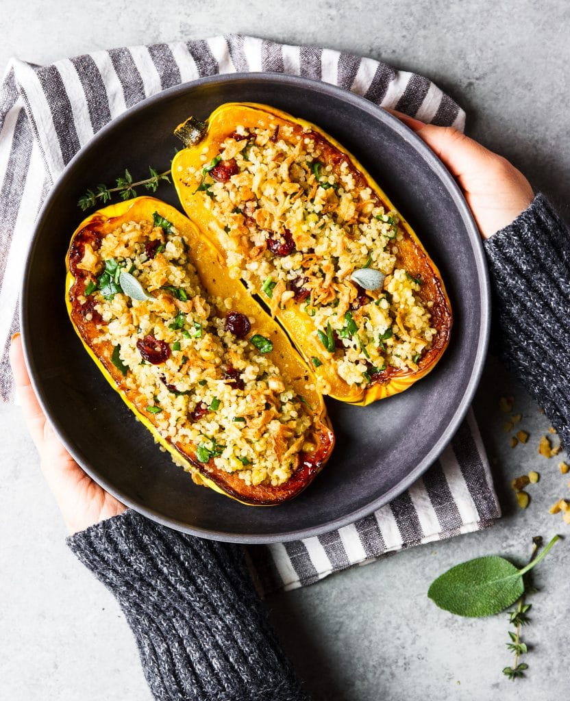 two delicata squash stuffed with quinoa and spinach, walnuts and cranberry on a black plate. A hand holding the plate.