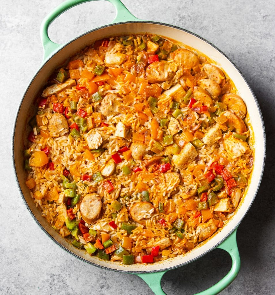 chicken jambalaya in a large green skillet with sausage, bell peppers and rice.