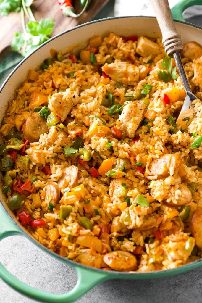 chicken jambalaya in a large green skillet with serving spoon.