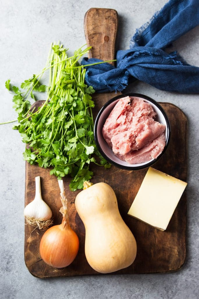 ingredients for a recipe on a wooden board. Ground turkey in a small white bowl. Fresh bunch of cilantro. A whole butternut squash, an onion and garlic. A block of cheese.