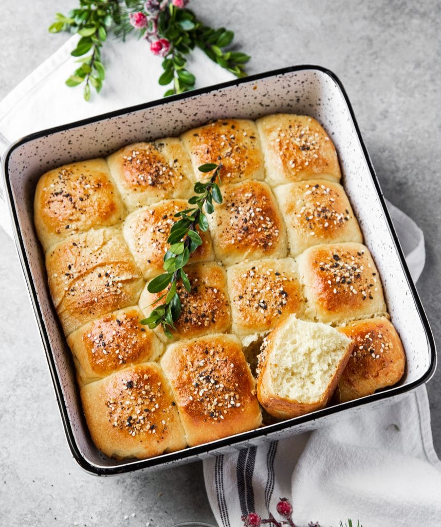 A dish with freshly baked dinner rolls. Festive herbs and a kitchen towel