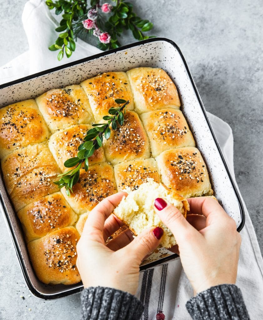 A hand grabbing a dinner roll from a baking dish.