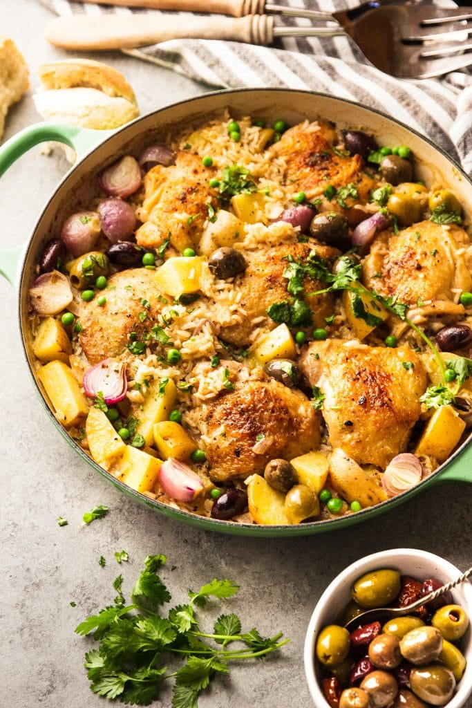 chicken thighs with rice in skillet with potatoes, red onions and olives