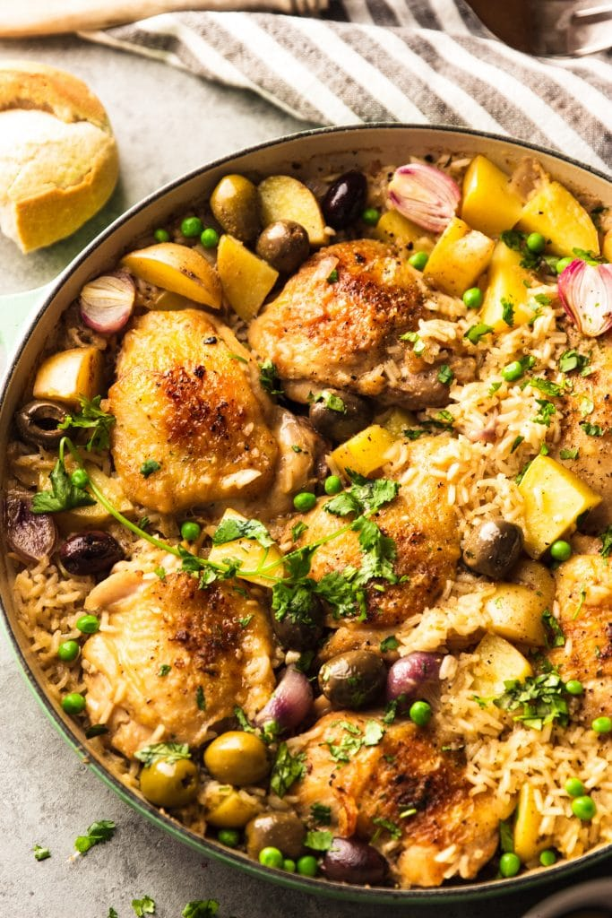 chicken thighs with rice in skillet with, potatoes, red onions and olives
