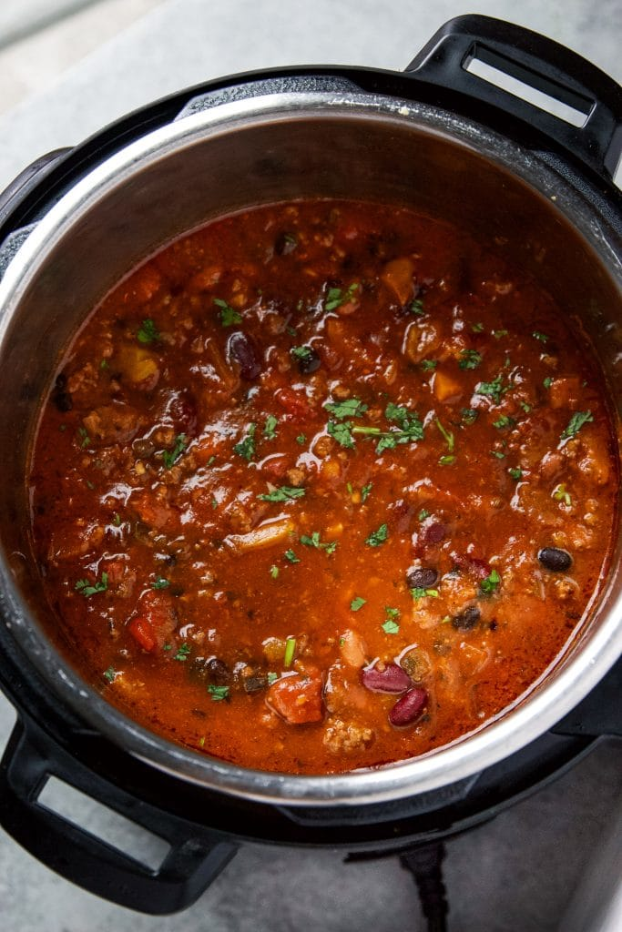 instant pot beef chili garnished with fresh cilantro.