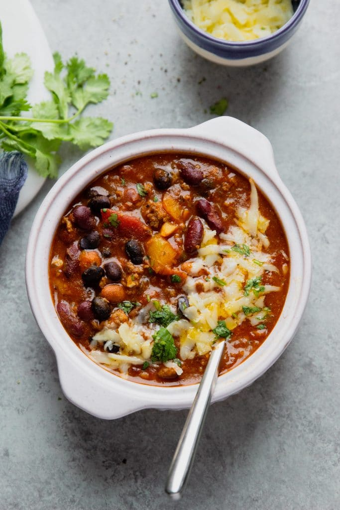 beef chili in a white bowl with a spoon. Melted cheese on top with fresh cilantro. A small blue bowl with extra cheese and a blue towel on the table.