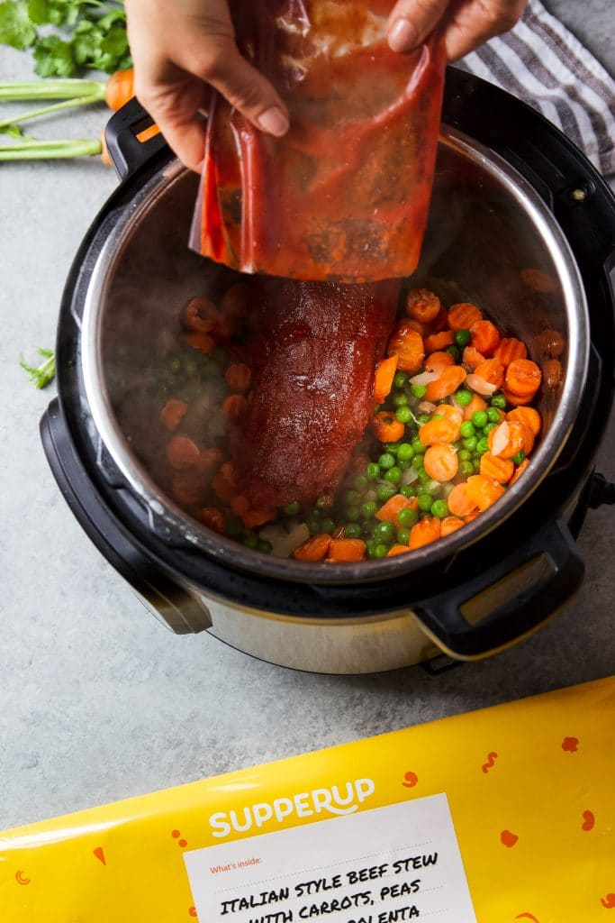A pouch with sauce and seasoning being added to the instant pot to make beef stew