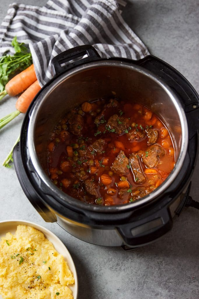 instant pot beef stew with carrots and peas. A plate with creamy polenta.