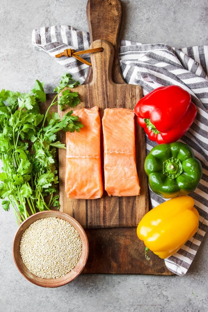 Ingredients for instant pot salmon and quinoa. Two salmon filets. Three colorful bell peppers. A bowl with quinoa and fresh cilantro on a wood cutting board.