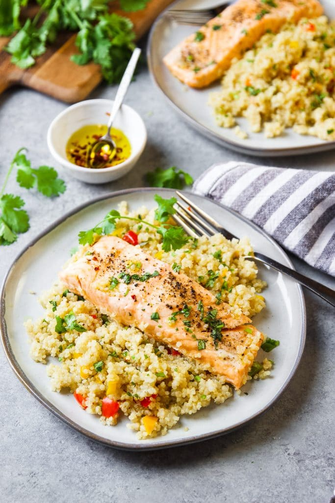 Salmon and quinoa on a plate with fresh cilantro. A small white bowl with olive oil and a mini spoon. A second plate with salmon and quinoa. Fresh herbs on a cutting board.