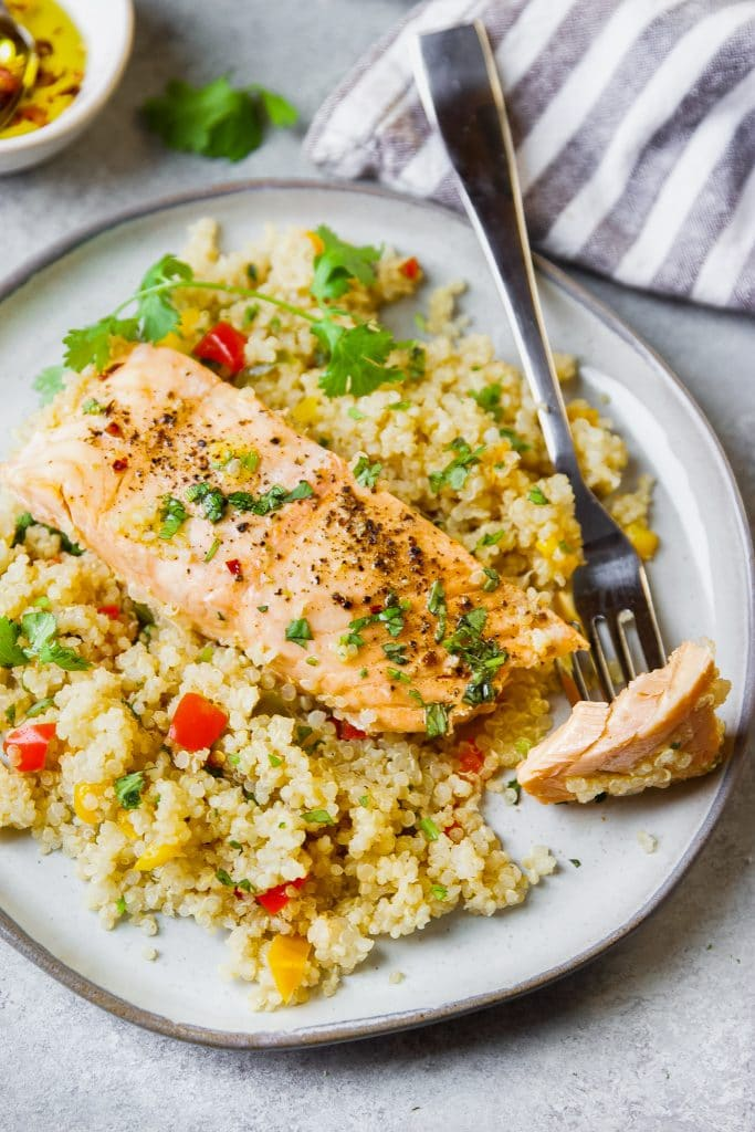 a plate with salmon and quinoa. a fork with a bite of salmon