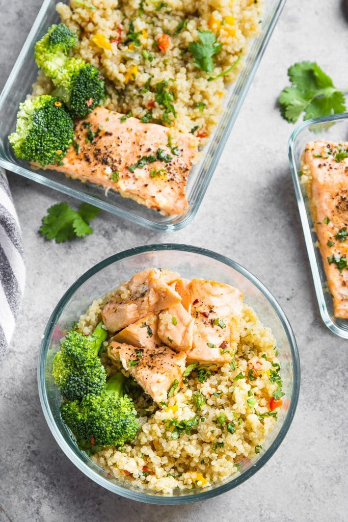 Three meal prepped glass containers with salmon and quinoa.