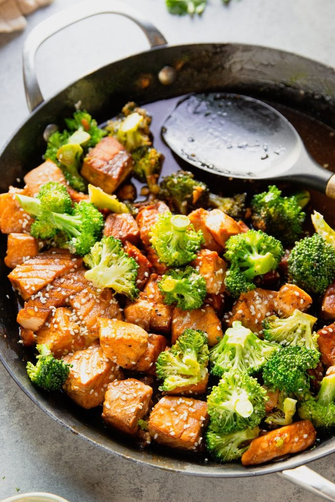 salmon and broccoli stir fy in a skillet. A wooden spatula
