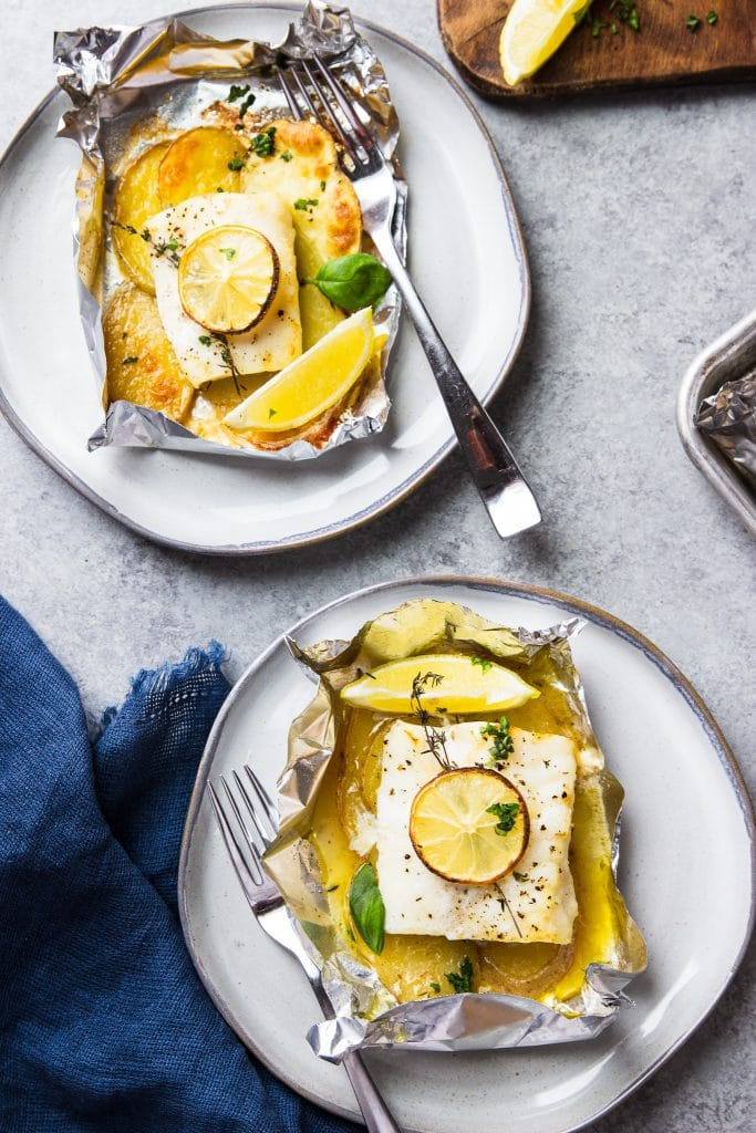 two fish in foil packets with potatoes on a plate