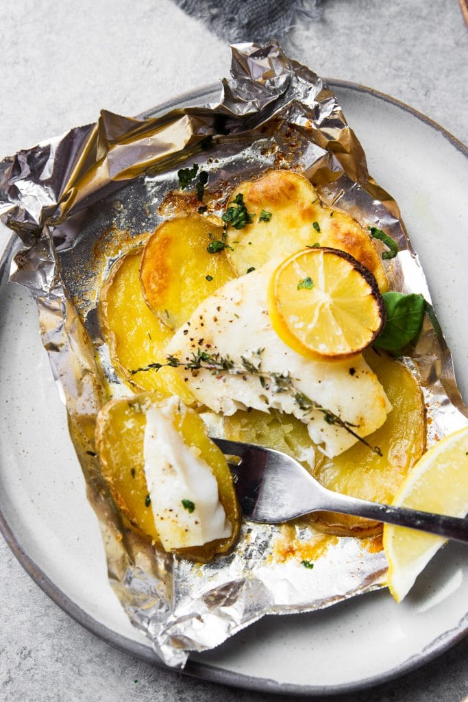 fish and potatoes baked in foil. A fish in foil packet on a plate with a fork