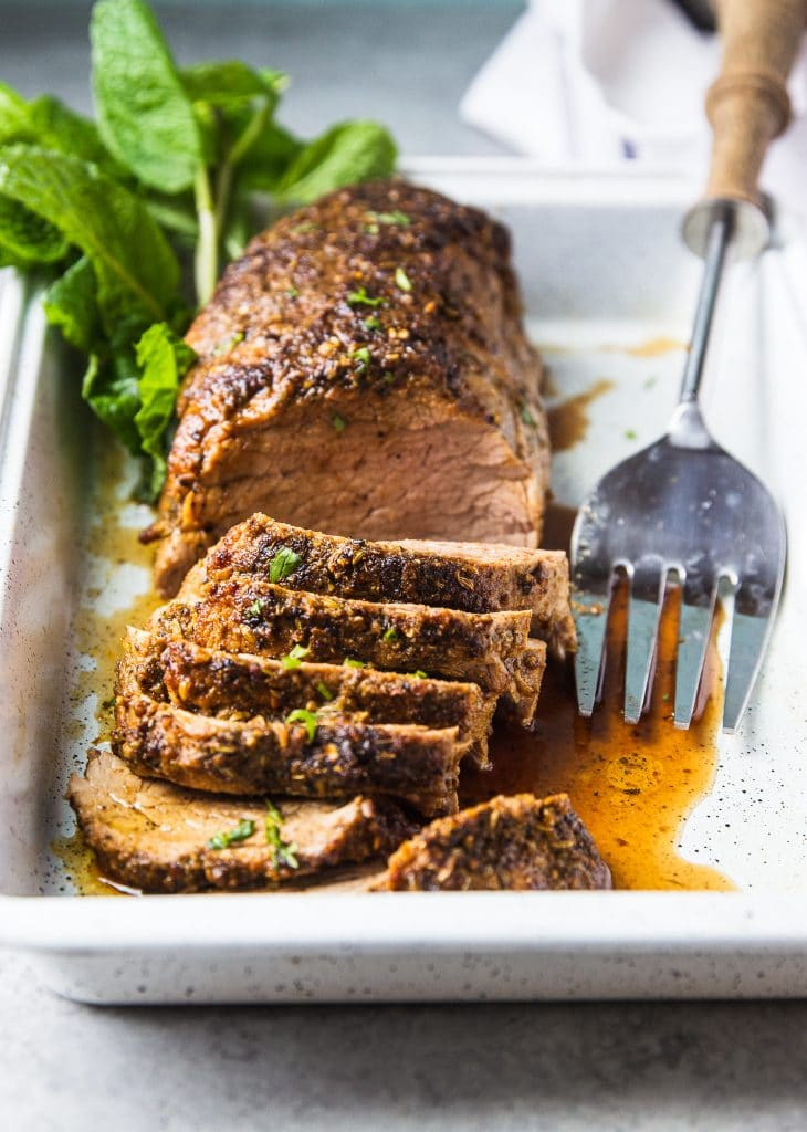 Sliced pork tenderloin in a baking pan seasoned with herbs. A large serving fork next to the pork.