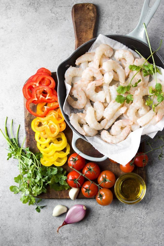 ingredients for shrimp stew (Brazilian moqueca de camarão); shrimp, bell peppers, vine tomatoes, oil, shallots, garlic and cilantro.
