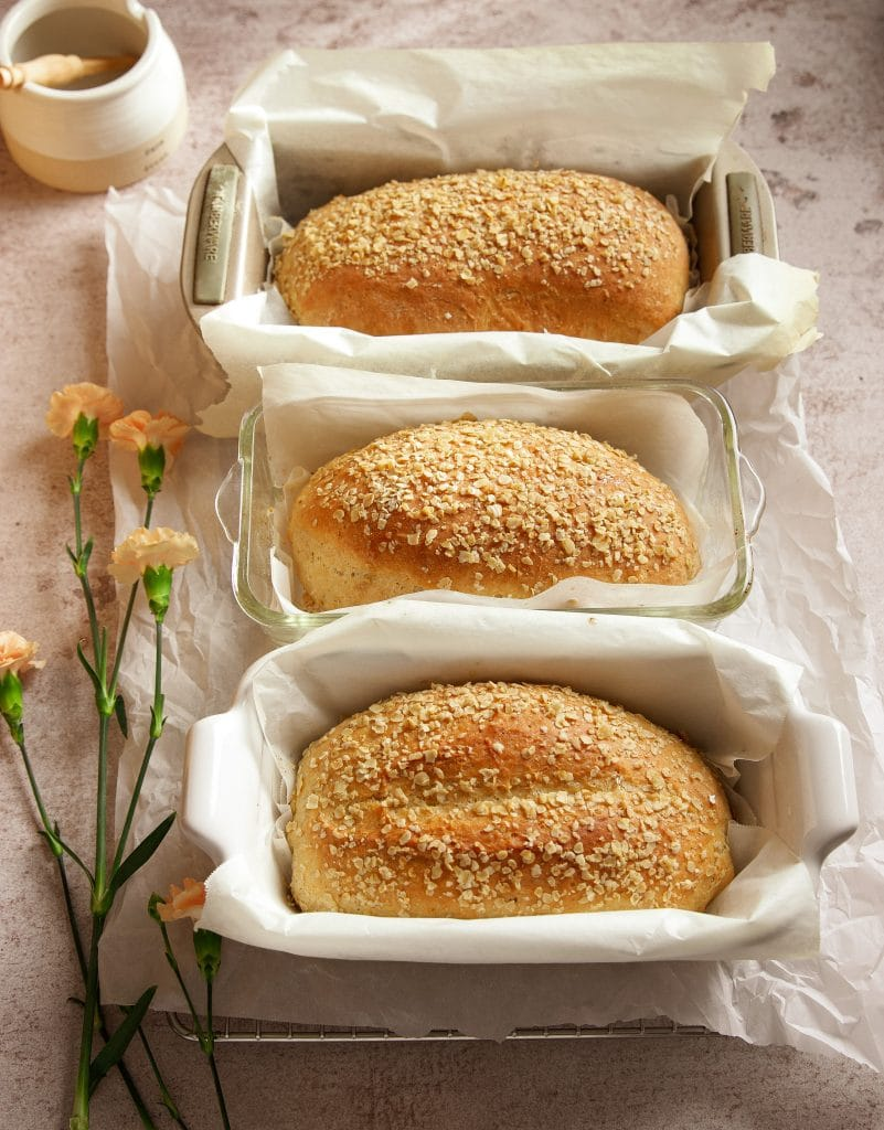 three loaves of honey oat bread on a cooling rack lined with parchment paper. A small pot with honey. Pink flowers on the table