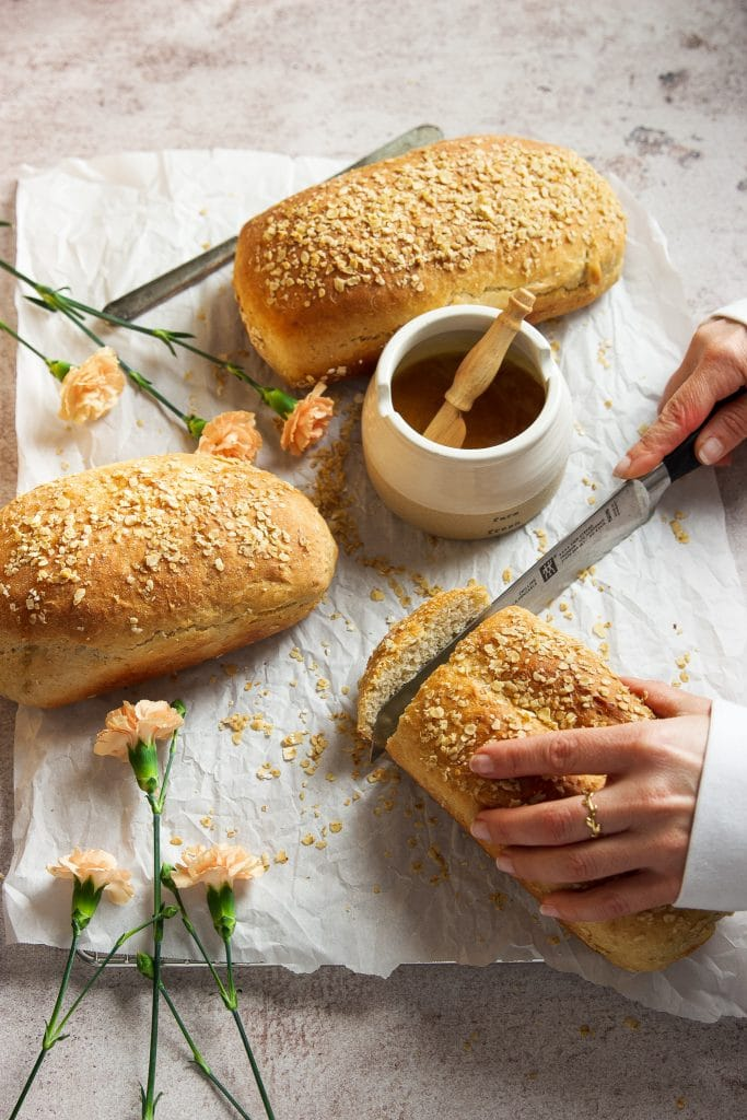 three loaves of honey oat bread on a cooling rack lined with parchment paper. A small pot with honey. A hand slicing one of the loaves of bread. Pink flowers on the table