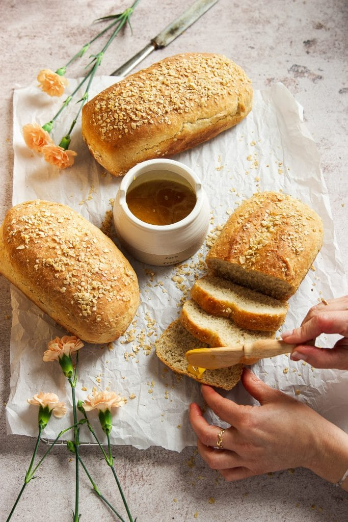 three loaves of honey oat bread on a cooling rack lined with parchment paper. A small pot with honey. A hand spreading honey onto the bread. Pink flowers on the table