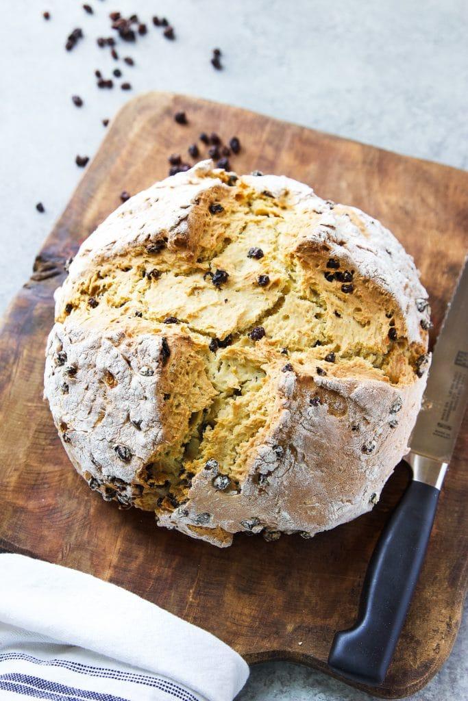 loaf of Irish soda bread on a wooden cutting board. A bread knife