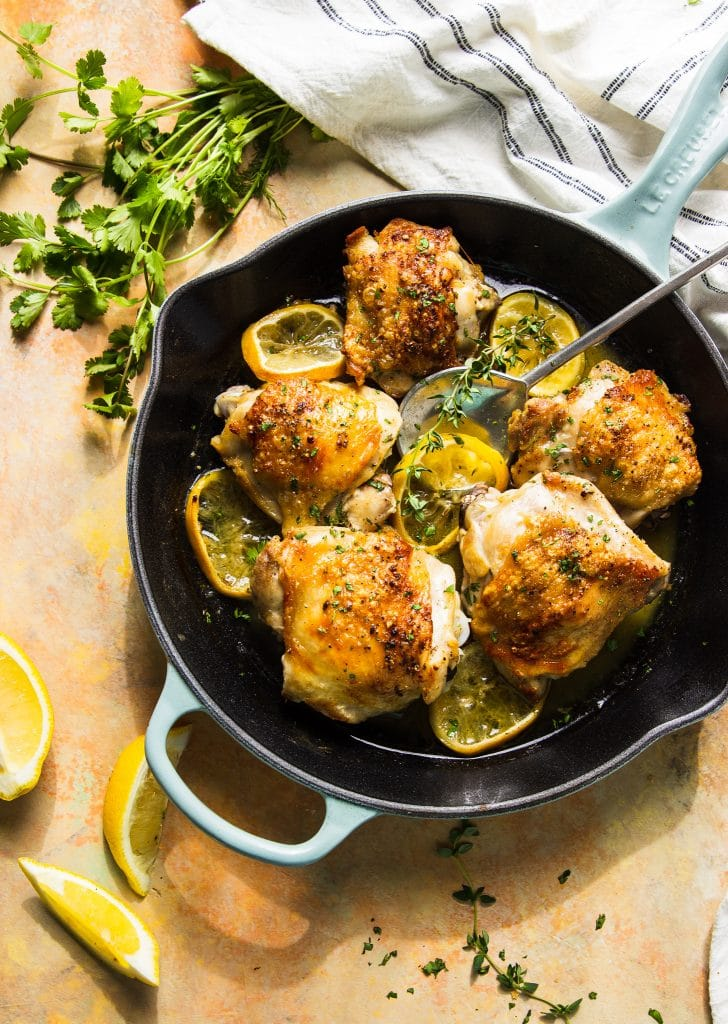 Butter chicken thighs in skillet with lemon slices and herbs