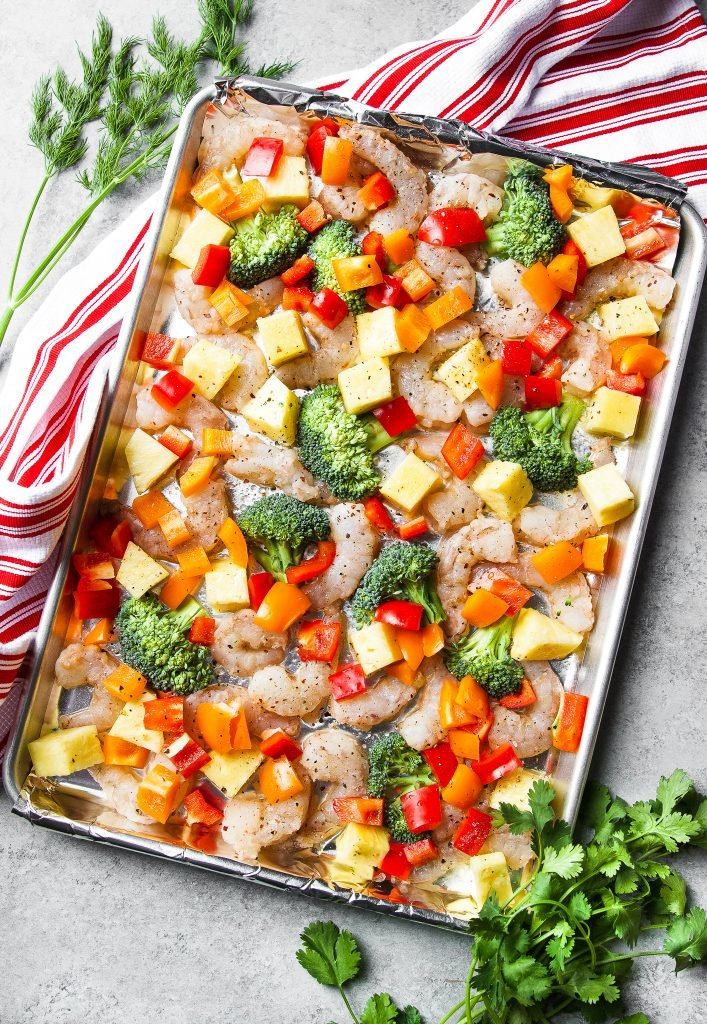 shrimp, pineapple, broccoli and bell peppers on a cooking sheet