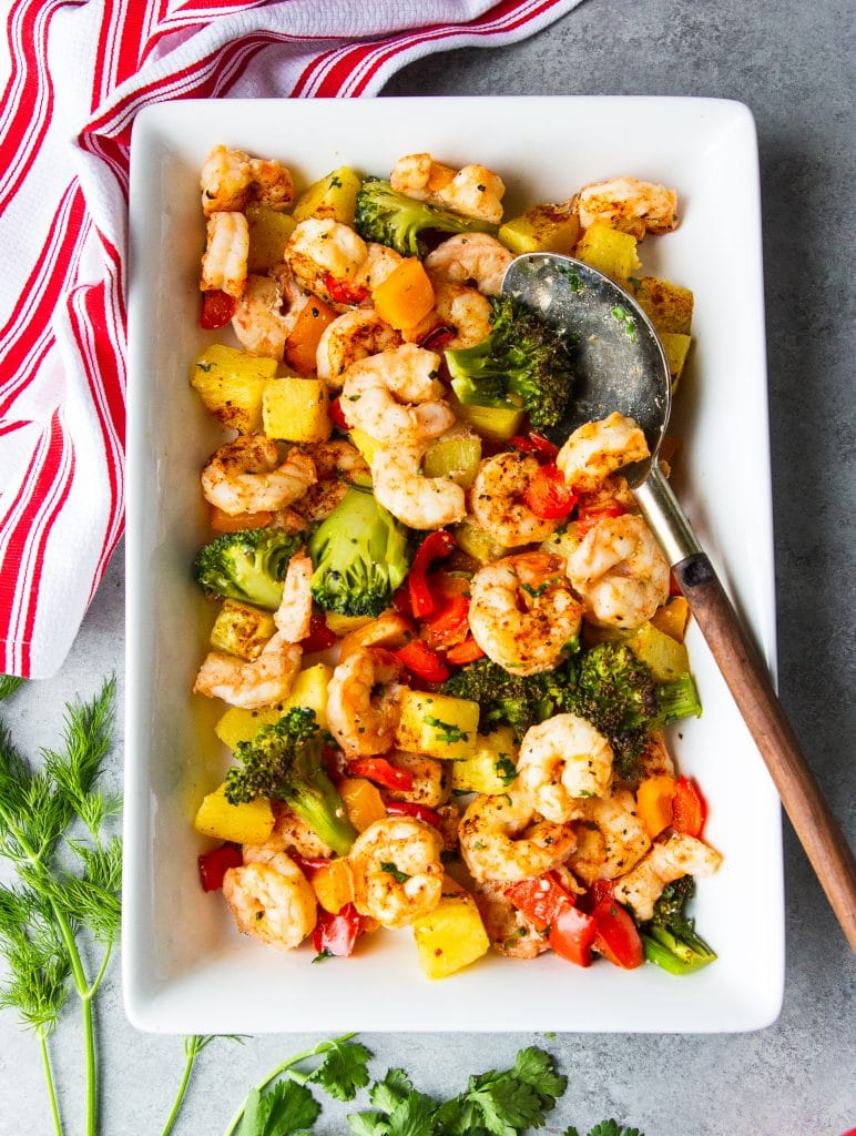 shrimp, broccoli, pineapple and bell peppers on a serving platter with a spoon.